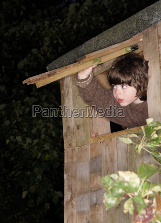 young boy at treehouse window