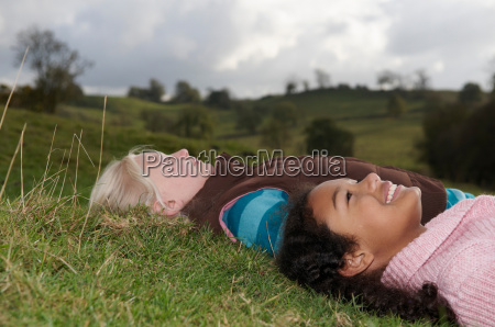two girls lying on grass looking
