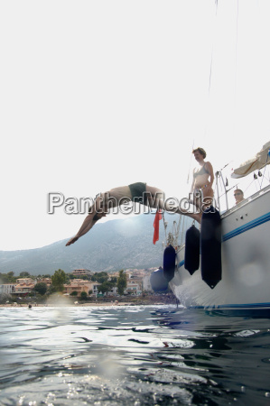 man diving into water from sailing