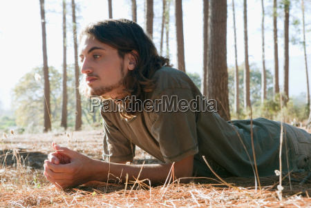 man looking at plant on forest