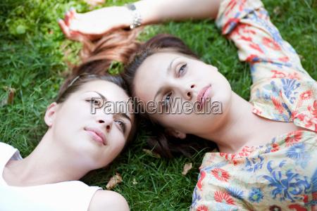 young women lying in grass