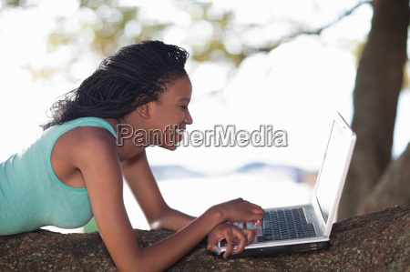 woman using laptop on a tree
