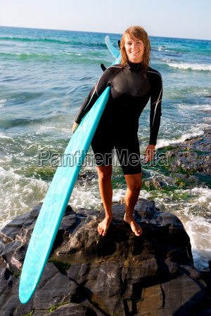 woman standing with a surfboard smiling