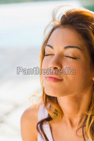 woman with eyes closed outdoors