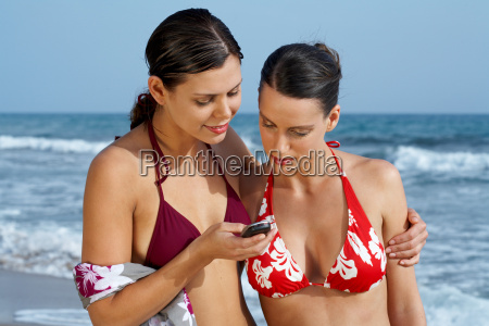 two young women looking at cell