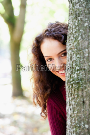young woman hiding behind tree
