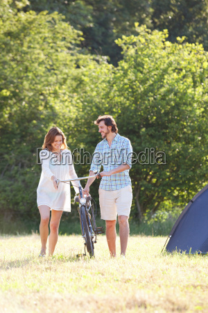 couple walking bike through field