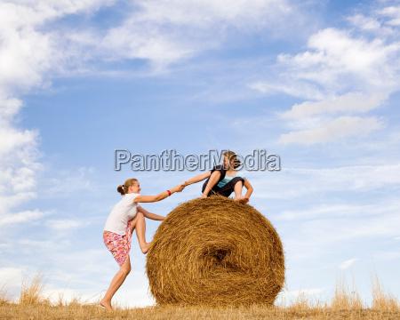 girl helping woman to climb hay
