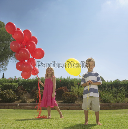 young children holding red balloons