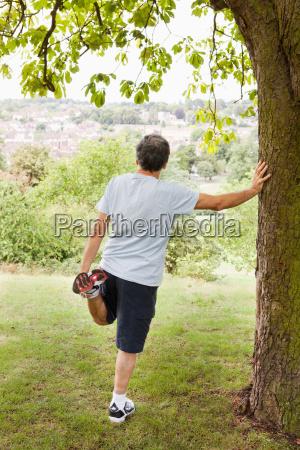 mature man stretches leg in park