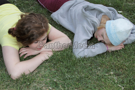 girls laying in grass at park