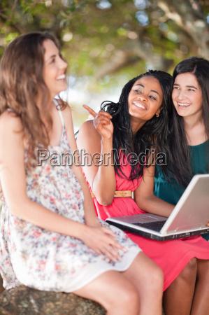 women using laptop whilst sitting on