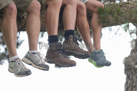 legs of three male hikers sitting