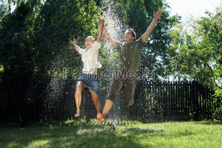 man and women jumping over sprinkler
