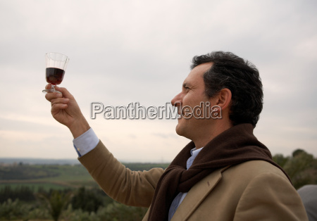 man looking at wine outdoors