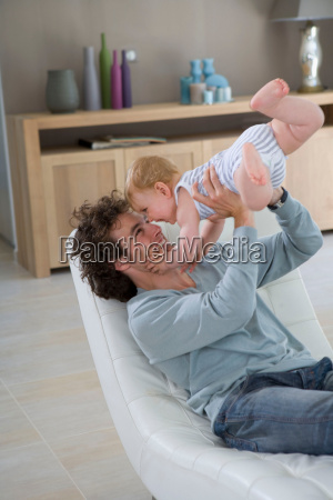 father holds up baby in chair