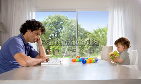 father and baby reading at table