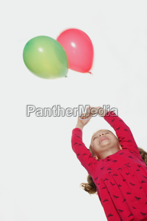young girl looking up at balloons