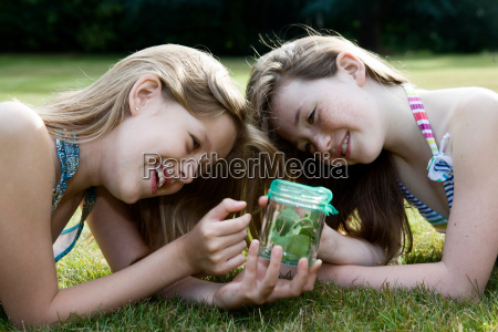 two girls looking at jar with