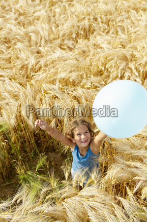 girl playing with balloon in wheat