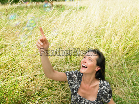 woman in a field soap bubbles