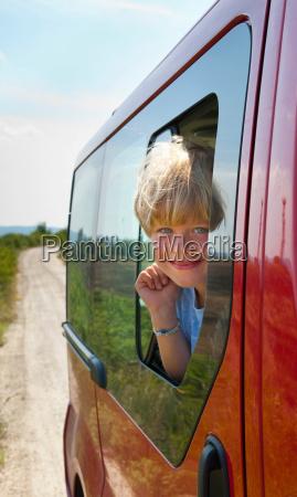 boy peering out car window