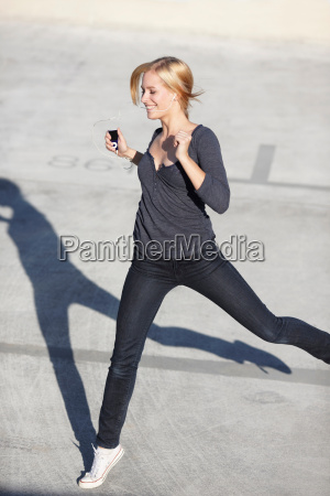 smiling women with mp3 player jumping
