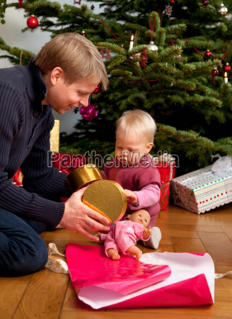father baby opening christmas present
