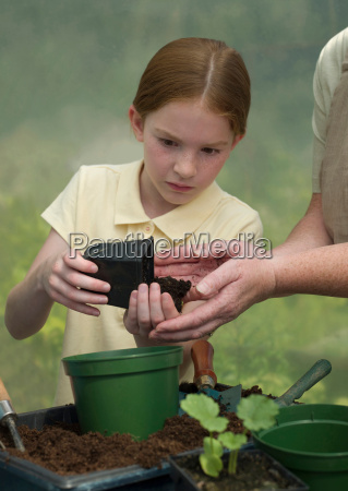young girl potting a plant