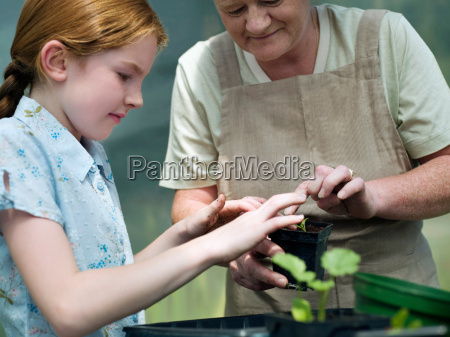 young girl and woman potting a