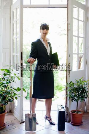 businesswoman holding shovel indoors