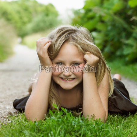 girl laying on grass in dirt