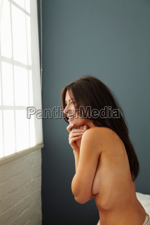 nude woman smiling in bedroom