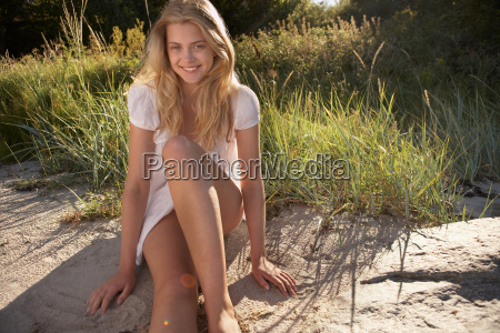 young woman sitting at edge of
