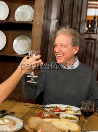 senior adult man toasting wine