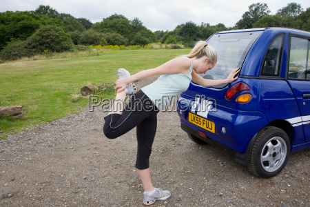 young woman exercising by electric car