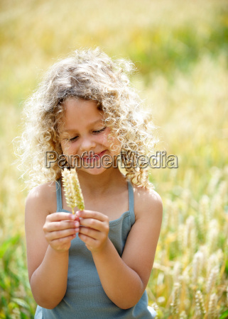 young girl with ears of corn
