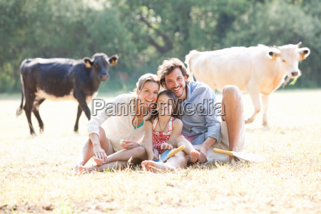 family sitting together in country field