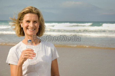 female drinking water on a beach