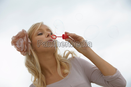 girl blowing bubbles flower in her