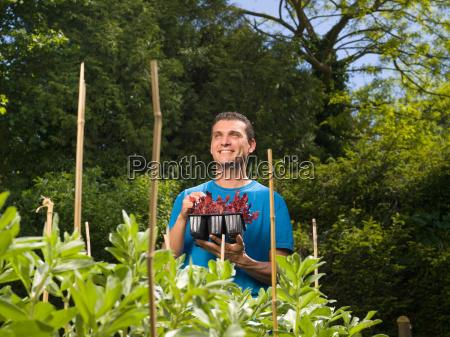 man in garden preparing to plant