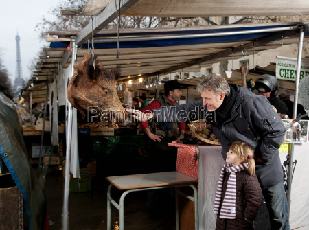 father touching boars head at market