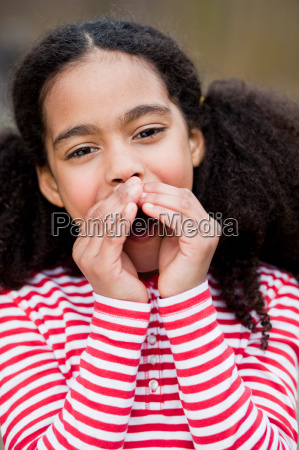 young girl with hands folded around