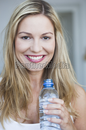 young woman holding bottle of water