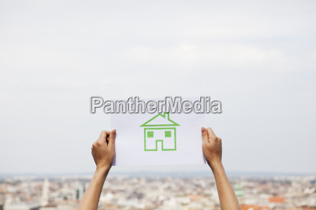 arms holding paper green house