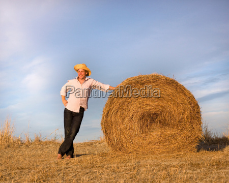 man standing by hay bale