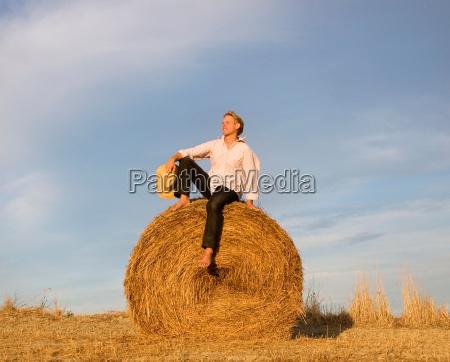 man sitting on hay bale