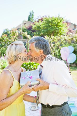 mature man offers present to partner