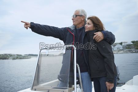middle aged couple on motor boat