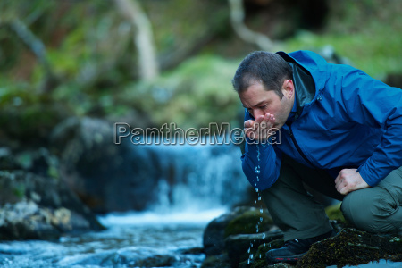 man drinking water from stream